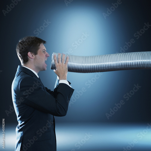 Caucasian businessman shouting into tube