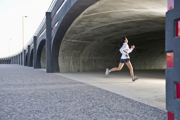 Hispanic woman running in tunnel