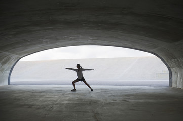 Hispanic woman stretching in tunnel