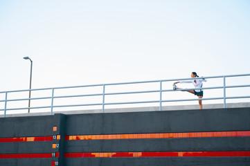 Hispanic woman stretching on railing