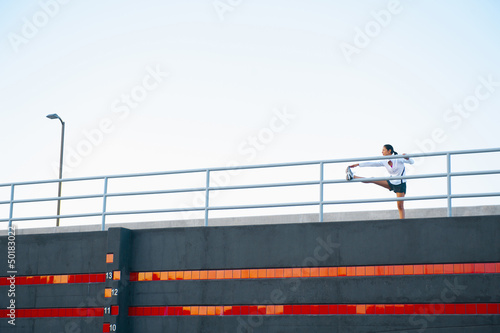 Hispanic woman stretching on railing