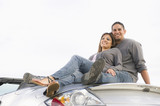 Hispanic couple sitting on convertible sports car