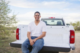 Hispanic man sitting on back of pick-up truck