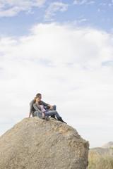 Hispanic couple sitting on large rock