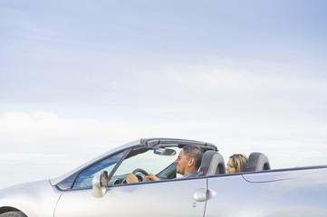 Hispanic couple driving in convertible sports car