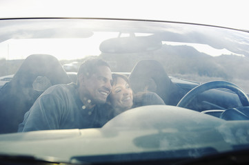 Hispanic couple unwinding in sports car