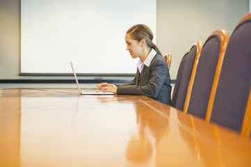 Hispanic businesswoman using laptop in conference room