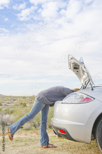Hispanic woman looking in trunk of sports car