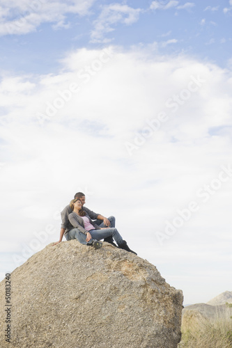 Hispanic couple sitting on large rock