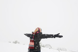 Hispanic woman with arms outstretched in snow