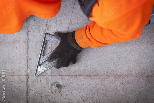 Construction worker marking cement