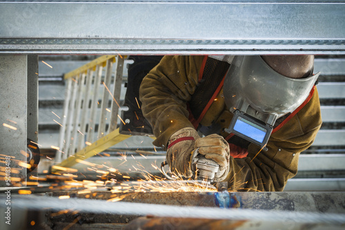 Construction worker grinding metal