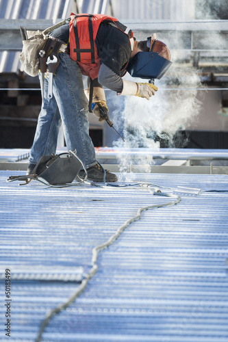 Caucasian construction worker welding floor
