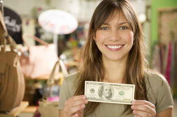 Hispanic woman holding cash in store