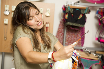 Hispanic woman holding clothing and talking on cell phone in store