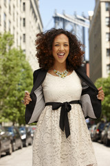 Grinning mixed race woman on urban street