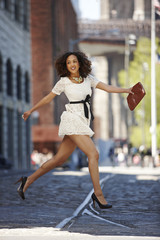 Glamorous mixed race woman running on urban street