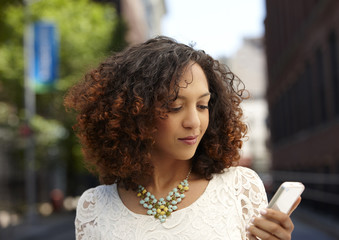 Mixed race woman using cell phone