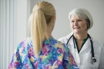 Caucasian doctor talking to nurse