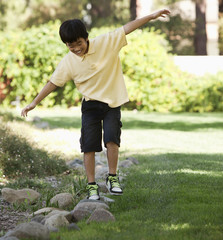 Korean boy balancing on stones in yard