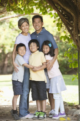 Asian family hugging outdoors