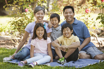 Smiling Asian family sitting on blanket in grass