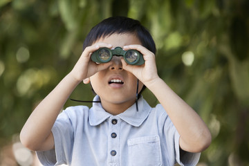 Korean boy peering through binoculars