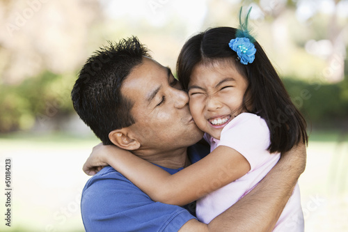 Asian father kissing daughter