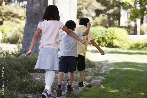 Korean children balancing on stones in yard
