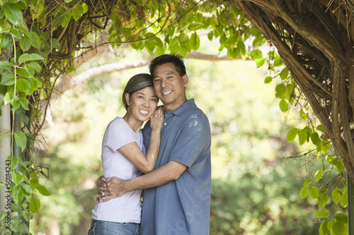 Asian couple hugging outdoors