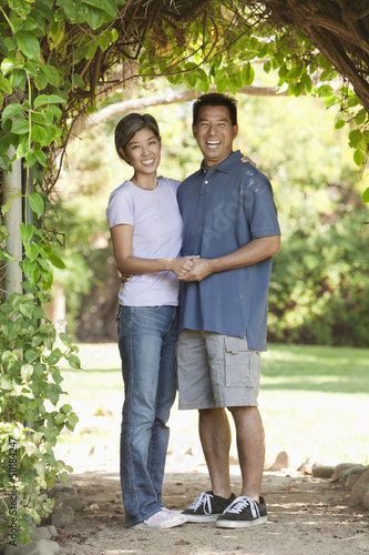 Asian couple holding hands in yard
