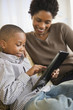 Black mother and son using digital tablet