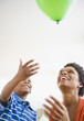 Black mother and son watching floating balloon