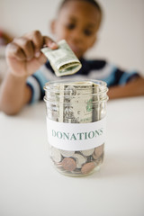Black boy putting money into donations jar