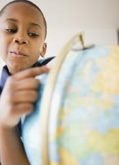 Black boy looking at globe