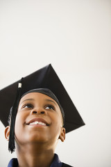 Smiling Black boy in graduation cap
