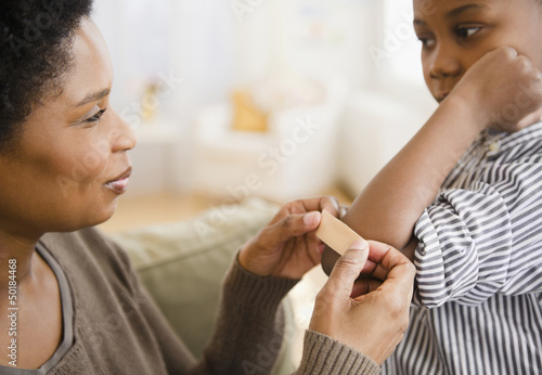 Black mother putting bandage on son's elbow