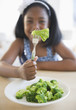 Black girl eating broccoli