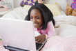 Black girl laying on bed using laptop