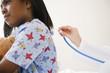 Doctor using stethoscope on Black girl in hospital