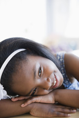 Smiling Black girl leaning on hands