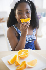 Black girl eating oranges