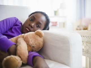 Black girl laying on sofa with teddy bear