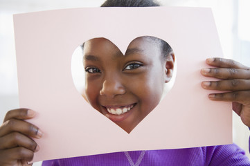 Black girl looking through heart-shaped opening in paper
