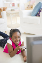 Black girl laying on floor watching television