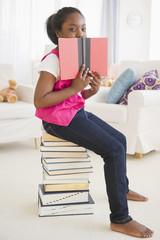 Black girl sitting on stack of books reading