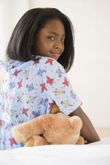 Black girl sitting on hospital bed