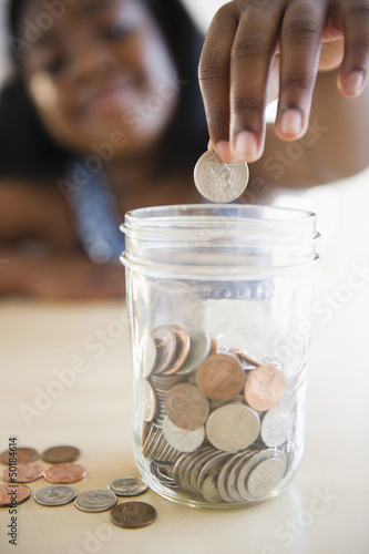 Black girl putting coins into a jar
