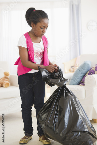 Black girl taking out the garbage