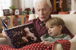 Caucasian grandfather reading book to grandson